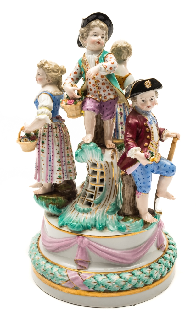 Sale FS39; Lot: 0566: A Meissen figural group of children after the model by J J.Kandler, the four children wearing 18th century dress and carrying flowers in baskets or in an apron, on circular plinth base moulded with pink ribbon swags above a leafy garland, underglaze blue crossed swords mark and impressed model no.B60, late 19th/early 20th century, 26cm [loss to one hand].