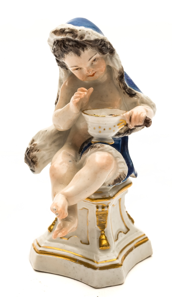 Sale FS39; Lot: 0568: A Meissen figure of a putto emblematic of Winter wearing a blue fur lined cloak and holding a pan of glowing coals and seated on a waisted sqare socle base, underglaze blue crossed swords mark, mid 18th century, 12.5cm high.