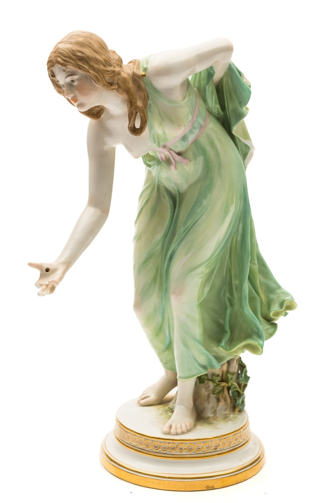 Sale FS39; Lot: 0569: A Meissen porcelain figure of a lady bowler modelled after the original by Walther Schott with a scantily clad bare foot lady stooping to throw a bowl stood before a stump on a circular gilt embellished base, painted blue crossed swords, incised Q 1806 with press number 121, late 19th/early 20th century, 30.5cm high, [devoid bowl and some digits, two chips].