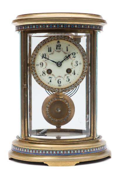 Sale FS39; Lot: 0732: Samuel Marti, Paris, a brass and enamelled oval four glass clock the eight-day duration movement striking the hours and half-hours on a gong and having a 'Brocot' regulation to the suspension, the backplate stamped with the trademark of the maker showing a Paris Exposition award, S Marti et Cie, Medaille d'Argent, 1889, and numbered 2259, the round white enamel dial having black Arabic hour numerals with coloured swags set between and decorative blued steel hands, the bezel set with cut paste brilliants, the gilded pendulum bob with matching brilliants, the oval brass four-glass case having bands of coloured champlevé enamel set to the base and top with grooved corners, height 29cm * Biography Samuel Marti was one of the most prolific French makers of the 1800s and was known to be working circa 1860 at Le Pays de Montbeliard, Paris making roulant blancs. Along with Japy Freres and Roux they set up a business in 1863 to market their movements to such firms as L'Epee. Their Paris address was Rue Vieille-du-Temple from 1870.