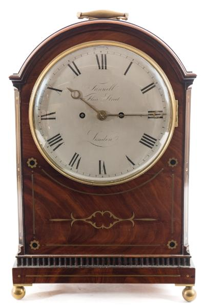 Sale FS39; Lot: 0734: Tunnell, Fleet Street London, a Regency mahogany bracket clock the eight-day duration, double-fusee movement striking the hours on a bell with the shaped backplate having engraved border decoration, the eight-inch round silvered dial engraved with black Roman numerals and engraved to the centre with the maker's name Tunnell, Fleet Street, London, with brass moon hands, the mahogany case having brass inlaid decoration to the front, with further inlay and scroll stops to the canted corners and brass fishscale side frets, surmounted by a brass carrying handle to the curved top and all standing on brass ball feet, height 43cm (handle down) 50cm (handle up). * Biography A John Tunnell is recorded as free of the Clockmakers Company in 1814 and a Liveryman from 1826, quite possibly moving to Deptford, Kent prior to 1847 where he is still recorded in 1849.