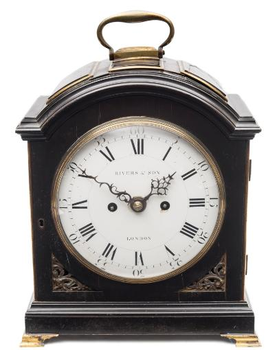 Sale FS39; Lot: 0736: Rivers & Son, London, a Georgian ebonised verge bracket clock the eight-day duration, five-pillar movement having a verge escapement and striking the hours on a bell with pull repeat and having a fully engraved backplate, the seven-inch round enamelled dial having black Roman hour numerals, Arabic outer five-minute numerals and signed Rivers & Son, London, with decorative blued steel hands, the ebonised case having a full opening front door with brass fret work below and brass edging, brass side frets, a three-pad top with brass mounts, surmounted by a brass carrying handle and standing on brass bracket feet, height 34cm (handle down): 38cm (handle up). * Biography David Rivers is recorded as working in Sweetings Alley, London being free of the Clockmakers Company in 1766 with the business becoming Rivers & Son in circa 1782 with an address in Cornhill, where they were successors to Daniel de St Jeu, Clockmakers to her Majesty. David died in 1815.