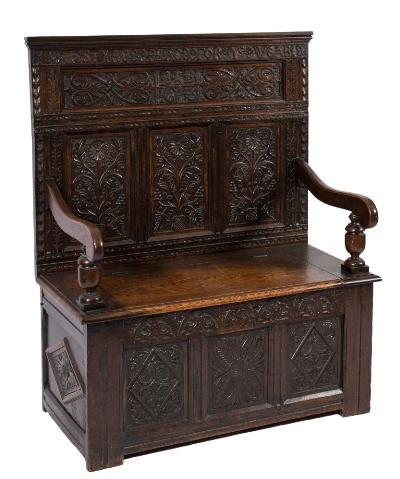 Sale FS39; Lot: 0765: A carved oak box settle, the rectangular back with ledge top rail and frieze panels inscribed 'Ye Restynce Place for Ye Wearie' and initials BB and date 1643, flanked by geometric scrolling acanthus, having triple panels with flowering and berried stems below, the plain hinged box seat with moulded arm supports and with lunette foliate frieze and triple lozenge geometric foliate panels below, 97cm (3ft 2in) long (part 18th & 19th Centuries).