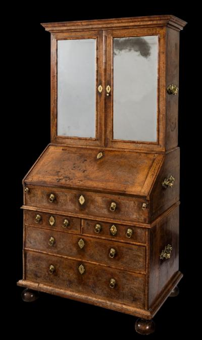 Sale FS39; Lot: 0783: A William and Mary walnut veneer and feather banded bureau cabinet, in three sections, the upper part with a moulded cornice, fitted with shelves, enclosed by a pair of bevelled mirror panel doors, the waisted lower part with central section having a crossbanded sloping hinged fall fitted with a ledge, enclosing a fitted interior with small drawers and pigeon holes with slides, having triple divided wells with sliding covers, containing two short and two long drawers to the section below, with brass ring handles, the sides each applied with three brass carrying handles, on later bun-shaped feet, 100.5cm (3ft 3 1/2in) wide, 190.5cm (6ft 3in) high.