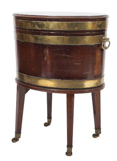 Sale FS39; Lot: 0793: A George III mahogany, inlaid and brass bound oval wine cooler on stand, the hinged moulded top bordered with boxwood lines enclosing a zinc lined interior, having brass carrying handles to the sides, the stand on square tapered splayed legs, terminating in brass cappings and castors, 57cm (1ft 10 1/2in) across.