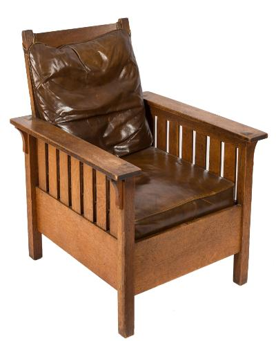 Sale FS39; Lot: 0893: An Arts and Crafts 'Morris' oak armchair in the manner of Gustav Stickley, having a curved bar back hung with a leather cushion and with plain broad and slatted arm supports, having a brown leather seat on square section legs.