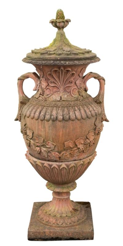 Sale FS39; Lot: 0901: A terracotta twin-handled pedestal urn and cover, the detachable top with radiating petals and pomegranate finial, the body with anthemion and vine pattern bands and swags and a reeded band, the detachable base with elongated leaves, fluted socle and square base, 155cm (5ft 1in) high.