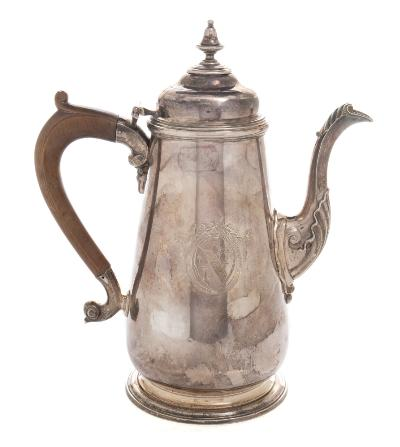 A George II chocolate pot maker William Parry, Exeter, 1747 crested, of tapered cylindrical form, the domed hinged lid with removable urn finial, acanthus decorated spout and wood scroll handle, raised on a circular spreading foot, 25cm high. 885gms, 28.48ozs.