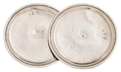 Sale FS39; Lot: 0105: A pair of George I Irish silver patens, maker John Hamilton, Dublin, 1723 crested, of plain circular form, raised on a waisted pedestal, 12.5cm diameter, 252gms, 8.11ozs.
