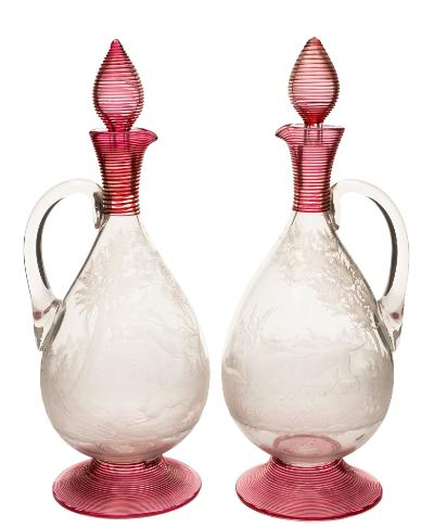 A pair of late 19th century engraved and applied glass claret jugs and stoppers probably Stevens and Williams, each with threaded cranberry bands to the foot, neck and stopper, finely engraved and intaglio cut, one with setters and game birds in a wooded landscape, the other with greyhounds chasing a hare, 30 cm.