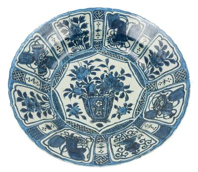 Sale FS39; Lot: 0420: A large Chinese blue and white Kraak charger painted with a jardiniere of flowers within a central shaped octagonal panel, the rim with alternating cartouches of flowers and auspicious objects within diaper borders, Wanli, 47cm diameter [restored crack].