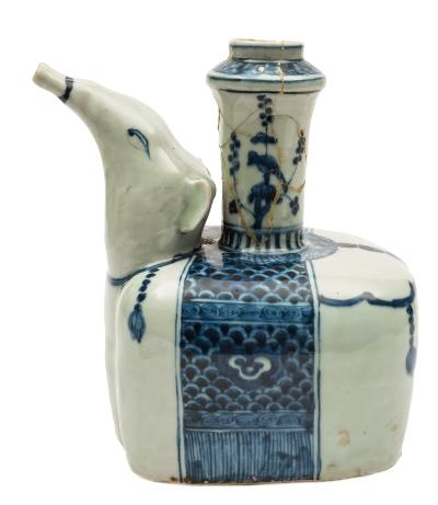 A Chinese blue and white 'elephant' kendi with head raised and hollow tusks forming the spout, the saddle cloth painted with ruyi heads on a scale ground, Wanli, 23cm high [neck damaged].