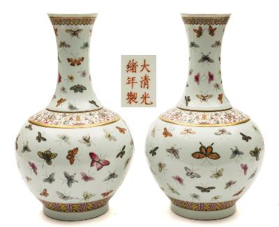 A pair of Chinese famille rose 'hundred butterfly' bottle vases painted overall with colourful butterflies between scrolling lotus, ruyi and lappet borders, iron-red six-character Guangxu marks, 40cm [one damaged].