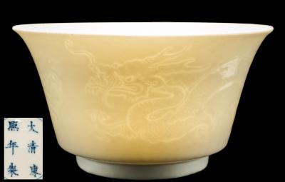 Sale FS39; Lot: 0466: A Chinese anhua dragon bowl with flared rim, the exterior carved with two dragons, the interior with a flaming pearl, apocryphal underglaze blue four-character Kangxi mark within double circles, 14cm diameter.