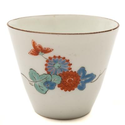 Sale FS39; Lot: 0479: A Japanese 'Kakiemon' beaker of tapered cylindrical form, painted in blue, turquoise and iron-red with flowering branches, brown line rim, 18th century, 7.5cm diameter.