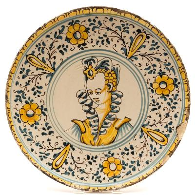 Sale FS39; Lot: 0485: An Italian maiolica crespina painted in blue, manganese and ocre with a head and shoulders portrait of a lady within a wide border of stylised flowers and foliage, probably 18th century, 28cm diameter [some chips and repair].