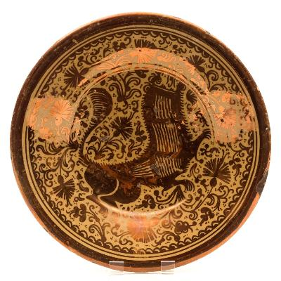 Sale FS39; Lot: 0488: An Hispano Moresque copper lustre pottery deep dish painted with a stylised lion on a ground of carnations and scrolling foliage within concentric band borders, on short footrim, probably Manises, circa 1700, 29cm diameter [flat chip to rim].