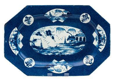 Sale FS39; Lot: 0525: A Bow blue and white porcelain octagonal dish painted with oval, fan and circular panels of floral sprays and Chinese landscapes on a powder blue ground, circa 1765, 37cm wide [minor chips].