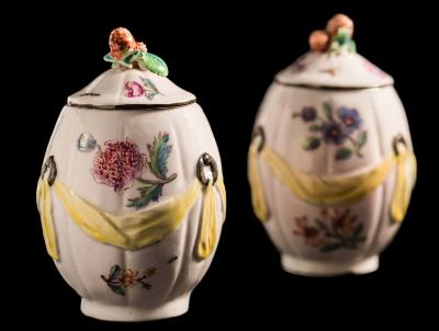 Sale FS39; Lot: 0532: A rare pair of Charles Gouyn, St.James's factory 'Girl-in-a-swing' tea canisters and covers of lobed ovoid form moulded with yellow drapery suspended from rings, the domed covers with applied strawberry finials, painted overall with floral sprays, insects and a caterpillar, one with incised cross mark to base, circa 1750-55, 13cm high [one with chip to foot rim, one cover with hairline crack, both finials with losses to strawberry leaves].