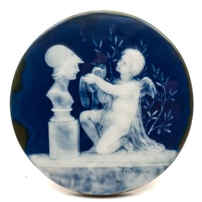 Sale FS39; Lot: 0538: Marc Louis Solon, a pâte-sur-pâte circular plaque applied and carved in white slip on a dark blue ground with Cupid wearing diaphanous robes and kneeling before a bust of Achilles, signed L Solon, late 19th century, 13cm diameter [flat chip to reverse] and stained wood frame.