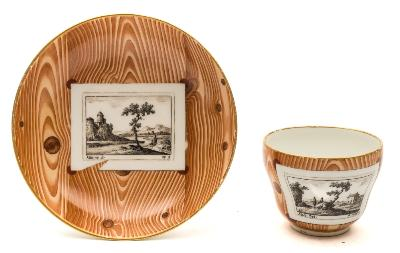 Sale FS39; Lot: 0558: A Vienna 'faux-bois' cup and saucer the cup of double ogee form with entwined twig handle, painted with black trompe l'oeil engravings of buildings in landscapes after Abel and Allaine on a faux-bois ground, underglaze blue shield mark with impressed date letter 84, diameter of saucer 13 cm.