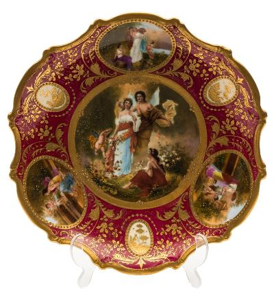 A 'Vienna' porcelain plate of silver shape the centre decorated with Cupid Psyche and others with three similarly decorated subsidiary panels reserved on a richly gilt burgundy border containing three medallions, the centre indistinctly signed, bears over glaze gold shield mark to reverse, 19th century, 30cm diameter.