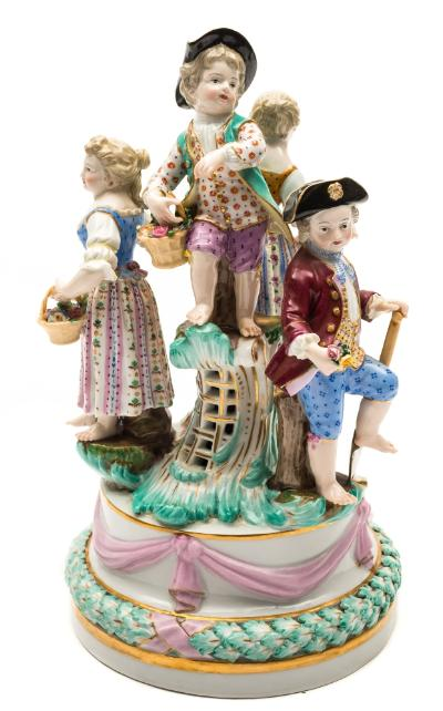A Meissen figural group of children after the model by J J.Kandler, the four children wearing 18th century dress and carrying flowers in baskets or in an apron, on circular plinth base moulded with pink ribbon swags above a leafy garland, underglaze blue crossed swords mark and impressed model no.B60, late 19th/early 20th century, 26cm [loss to one hand].