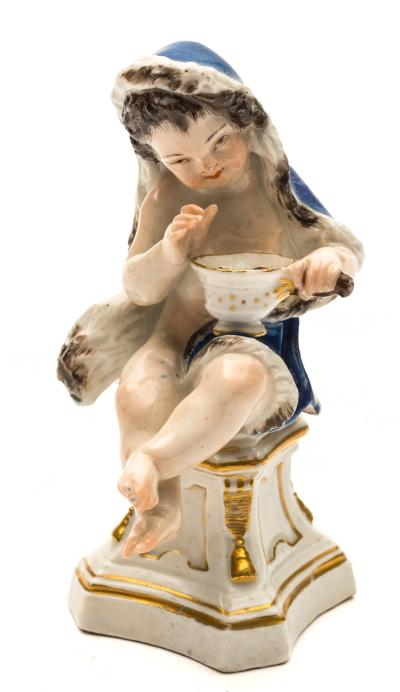 A Meissen figure of a putto emblematic of Winter wearing a blue fur lined cloak and holding a pan of glowing coals and seated on a waisted sqare socle base, underglaze blue crossed swords mark, mid 18th century, 12.5cm high.