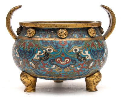 Sale FS39; Lot: 0607: A rare Chinese cloisonné enamel and gilt-bronze tripod censer, Ming Dynasty the globular body with twin arching reeded handles ending with ruyi heads and eight wave pattern bosses below the rim, decorated with a design of four taotie masks amongst scrolling foliage with a band of archaistic dragons above, three large lotus blooms to the underside in green, yellow, blue, brown, white and black enamels on a turquoise ground, on lotus bud cabriole legs, 21cm wide, 16cm high. * This fine censer was purchased at a house sale in Devon circa 1964/65 by the late husband of the present owner. He attended the sale with the intention of buying a Georgian tallboy, which he did, but when viewing saw the censer, liked the colour of the enamels and purchased it for a modest sum. It was used for several years as a plant pot but after being itemised in a late 1970s insurance valuation, was 'upgraded' to a desk tidy for paper clips and pens.