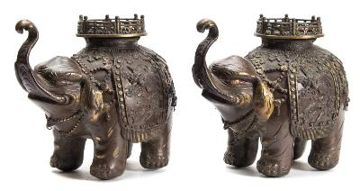 A pair of Japanese patinated bronze elephant incense burners each caparisoned elephant with pierced howdah and elaborate fittings and hangings cast with birds, blossom and scrolling foliage, Meiji, 21 cm.