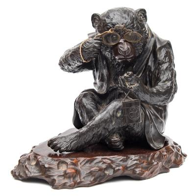 A Japanese bronze study of a monkey seated wearing a jerkin, holding a pair of spectacles in his right hand whilst inspecting, a netsuke held in his left hand, cast signature to the base, Hideyoshi kansei on a polished wood stand. Meiji period, height of figure not including stand 15cm.