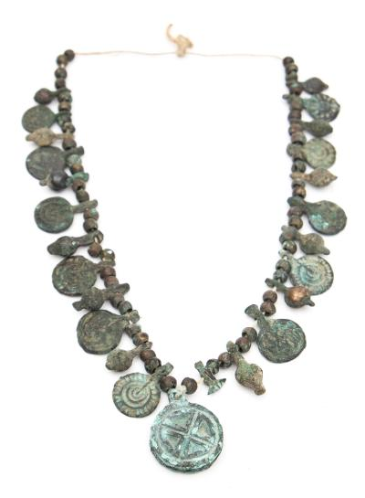 A group of Byzantine bronze amulets and beads 5th-7th century, threaded on a cord.