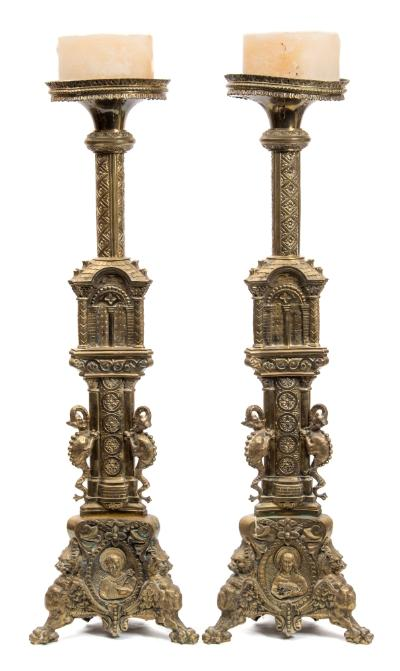 A large pair of 19th century brass candlesticks in the Italianate style, the circular drip trays on a foliate decorated columns and triangular shaped arched supports, raised on a further column with dragon buttresses, on swept grotesque mask feet, 92.5cm high.