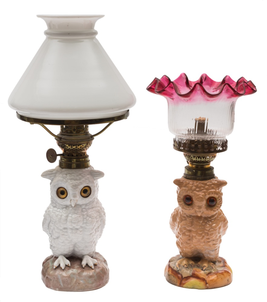 Sale FS40; Lot: 0629: Two Continental table lamps in the form of owls each seated bird with glass eyes, one with milk glass shade, the other in cranberry and clear glass, early 20th century, 27 and 34 cm.