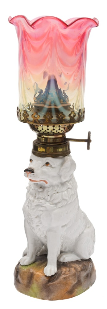Sale FS40; Lot: 0631: A Continental porcelain table lamp in the form of a dog seated on a mound base, with cranberry and vaseline glass shade and chimney, early 20th century, 28.5 cm.