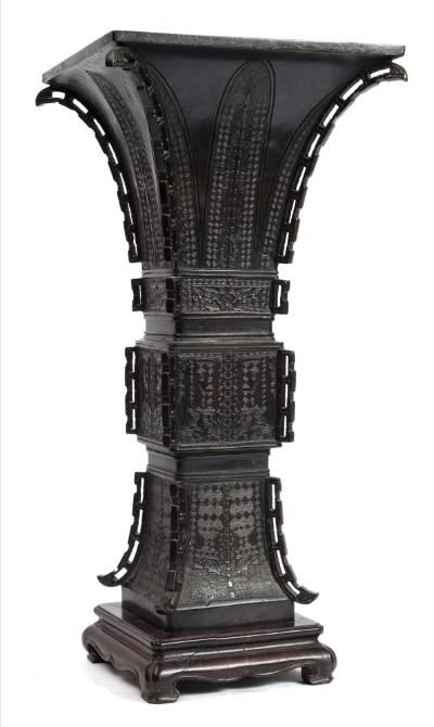 Sale FS40; Lot: 0679: A large Chinese bronze vase, Gu of square section, the corners with pierced vertical flanges, cast with lappets and taotie masks on a leiwen ground, 18th/19th century, 46cm and wood stand.