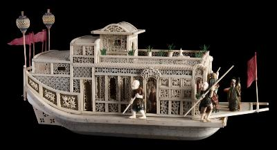 Sale FS40; Lot: 0687: A 19th century Cantonese carved ivory pleasure junk the pagoda style superstructure with trellis decorated panels, with four figures on the bow, four oarsmen and reclining figures to the interior, the stern with two lanterns and four pennants, 37cm long, some losses, on a polished mahogany stand with glazed dome.