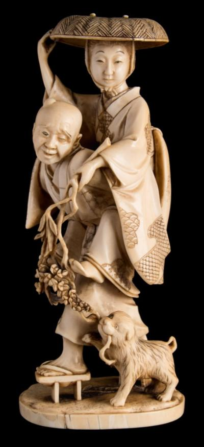 Sale FS40; Lot: 0711: A Japanese carved okimono of a semi-blind river crossing assistant carrying a young woman on his back with a dog holding onto a spray of flowers, signed Kozan (Takatama), Meiji period, 16.5cm high.