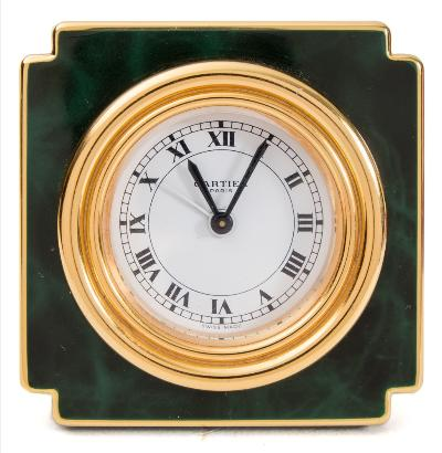 Sale FS40; Lot: 0802: le Must de Cartier, Paris Alarm Clock a gilt-brass and green enamel alarm clock, the round white dial having black Roman hour numerals, baton hands, alarm setting hand and signed le Must de Cartier, Paris, the shaped case stamped to the rear Cartier, Paris, and to the easel stand Swiss Made, 7512 14276, height 7.2cms.
