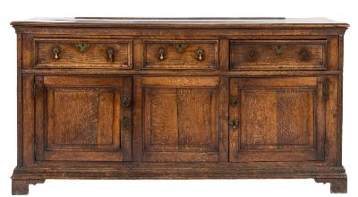 Sale FS40; Lot: 0906: An 18th Century oak rectangular dresser base, the top with a moulded edge, containing three moulded panel frieze drawers and with cupboard below, enclosed by a pair of fielded panel doors flanking a central fielded panel, on bracket feet, 167.5cm (5ft 6in) long.