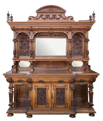 Sale FS40; Lot: 0969: By Wolfe & Hollander Ltd. A monumental Victorian carved walnut, burr veneered and burr oak breakfront sideboard, the shelved and mirrored superstructure with a turned gallery and shell and ribbon tied laurel garland pediment, a moulded dentil cornice with foliate decorated cushion frieze, on fluted and turned acanthus columns with scroll capitals, the domed flanking panels with masks, scrolling foliage and laurel garlands, the lower part with a gadrooned edge, having a central frieze drawer with cupboard below with a sliding cellarette, enclosed by a pair of doors with horned mask and acanthus scroll decoration flanked by open panelled recesses with square section tapered columns on a moulded plinth base with bun feet. 229cm (7ft 6in) long, 290cm (9ft 6in) height. Bearing an ivory plate Wolfe & Hollander Ltd., 262, 263, 264 Tottenham Court Road, London W.