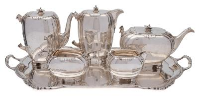 An Elizabeth II silver six-piece tea and coffee service, maker Mappin & Webb, Sheffield, 1959 of ovoid form with reeded angles, raised on beaded feet, includes tea pot, coffee pot, hot water pot, cream jug, sugar basin and rectangular serving tray with loop carrying handles, total weight of silver 4646gms, 149.38ozs.