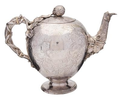 Sale FS40; Lot: 0089: A William IV silver teapot, maker Charles Reily & George Storer, London, 1836 of globular form, the hinged lid with strawberry finial and all over foliate engraved decoration, with naturalistic handle and ivory insulators, on a spreading circular foot, 17cm high. 702gms, 22.58ozs.