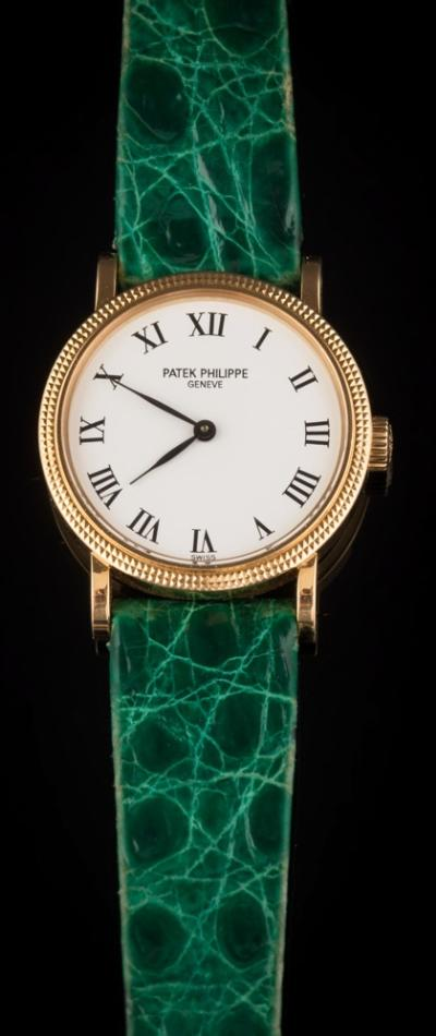 Patek Philippe. A lady's 'Patek Philippe' wristwatch the signed circular, white enamelled dial with Roman numerals within a grained bezel surround on green coloured strap stamped 'Patek Philippe Geneve' contained in a signed maroon leather case, together with certificate of origin confirming date of purchase as '1997'.