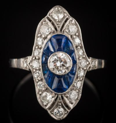 An early 20th century platinum, sapphire and diamond marquise-shaped cluster ring with central round diamond approximately 0.25ct, millegrain-set within a surround of tapering keystone shaped sapphires and smaller diamonds, ring size N 1/2.