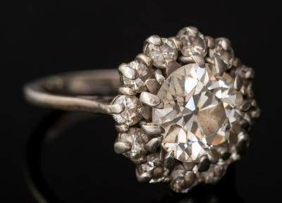 Sale FS40; Lot: 0320: A diamond cluster ring the round old, brilliant-cut diamond approximately 8.9mm diameter x 5.4mm deep, estimated to weigh a total of 2 7cts, within a surround of twelve round, brilliant-cut diamonds, the shank un-marked, 6.4gms gross weight, ring size N 1/2.