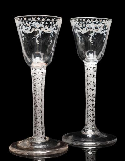 A pair of 'Beilby' white enamelled wine glasses each with round funnel shaped bowl decorated below the rim with a geometric and foliate scroll band, set on a straight double series opaque twist stem containing a pair of eight ply bands around solid spiral threads, on a conical foot, circa 1770, 15cm high.
