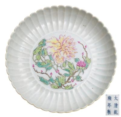 Sale FS40; Lot: 0550: A Chinese yellow ground famille rose 'peony' dish with fluted rim, the centre painted with a large peony spray, with lemon yellow ground to the underside, apocryphal underglaze blue six-character Qianlong mark within double circles, 18cm diameter.