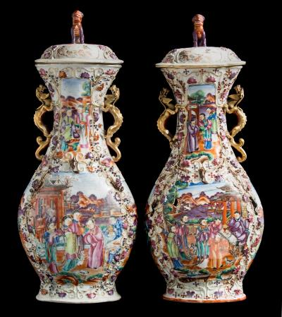 A pair of large Chinese famille rose porcelain export vases and covers each of quadrilobed form with chilong handles the domed cover with shi-shi knop, the body moulded with fruiting vine and tree rats and decorated in the 'Mandarin' palette with panels containing numerous figures in pavilion gardens, Qianlong, 50cm high, [one damaged and glued].