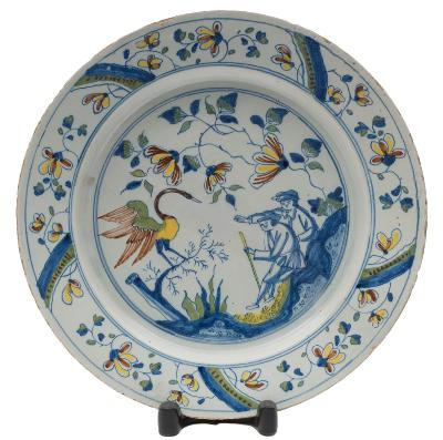 Sale FS40; Lot: 0560: A Bristol polychrome delftware dish painted with two men seated on rockwork pointing towards a large heron-like bird within a panelled floral border, mid 18th century, 34cm diameter [glaze cracks to the reverse, minor glaze losses].